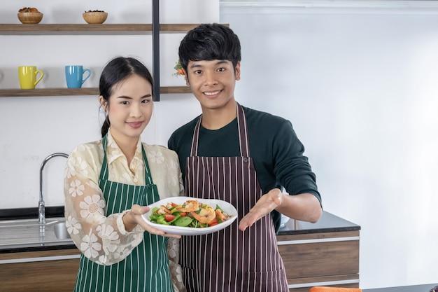 Jonge mannen en aziatische meisjes tonen garnalensalade