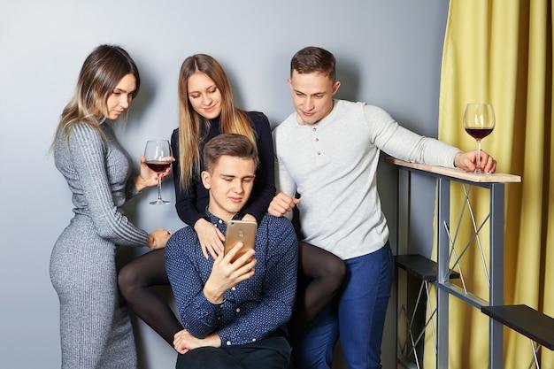 Jonge mannen en vrouwen bekijken foto's van studentenfeest op scherm van mobiele telefoon of smartphone.
