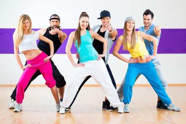 Jonge mannen en vrouwen dansen zumba moderne groepschoreografie in dansschool