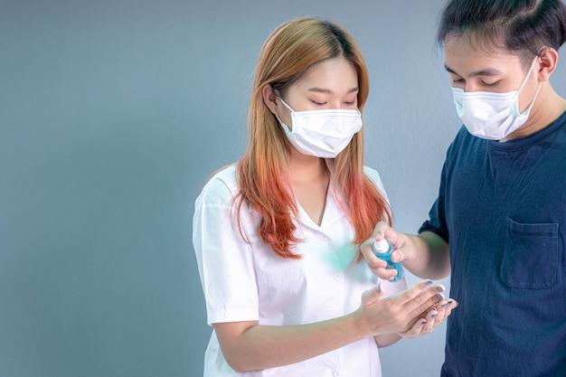 Jonge mannen en vrouwen die maskers dragen, gebruiken alcoholspray of alcoholische antiseptische gel om de handen te reinigen en ziektekiemen te voorkomen. covid-19 en persoonlijk hygiëneconcept.