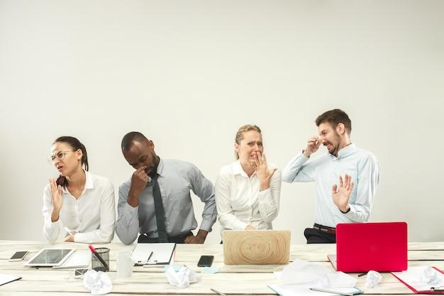 Jonge mannen en vrouwen die op kantoor zitten en aan laptops werken. emoties concept