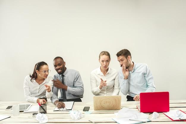 Jonge mannen en vrouwen die op kantoor zitten en op laptops werken. emoties concept