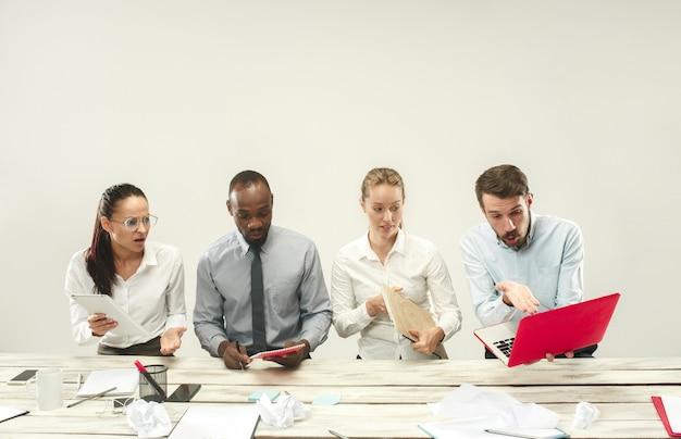 Jonge mannen en vrouwen die op kantoor zitten en op laptops werken.