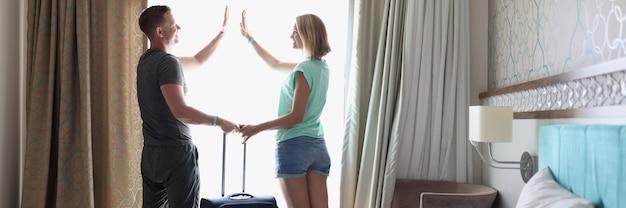 Jonge mannen en vrouwen met koffer die vijf handen geven in hotelkamer