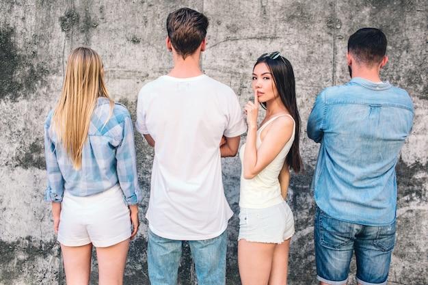 Jonge mannen en vrouwen staan voor de grijze muur en een vrouw vraagt om stilte