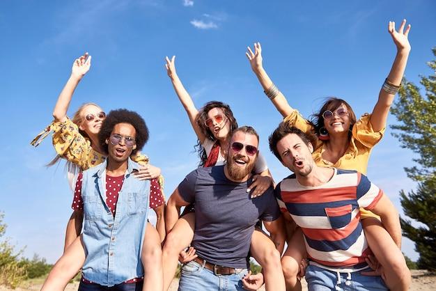 Jonge mannen geven zijn vriendinnen een ritje op de rug