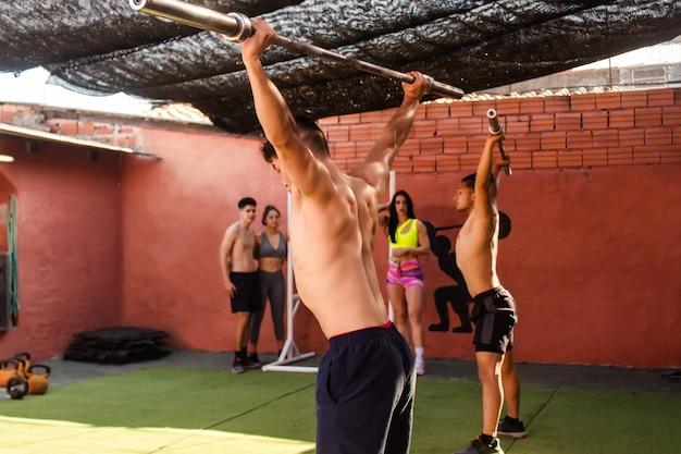 Jonge mannen grijpen terwijl hun vrienden rusten. crossfit training.