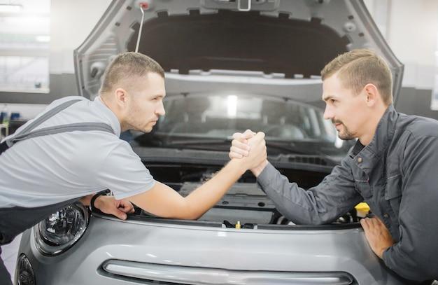Jonge mannen maken een deal tussen elkaar. ze leunen tegen de auto en houden elkaars handen vast. het voorste deel van de carrosserie is geopend.