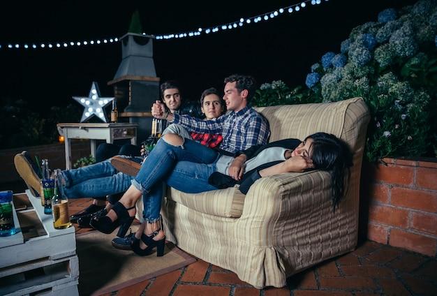 Jonge mannen praten en hebben plezier in een buitenfeest terwijl de vrouw op de bank ligt te slapen. vriendschap en vieringen concept.