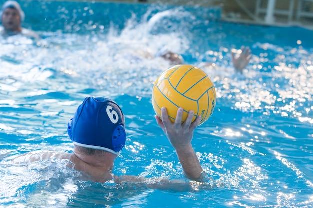 Jonge mannen spelen waterpolo
