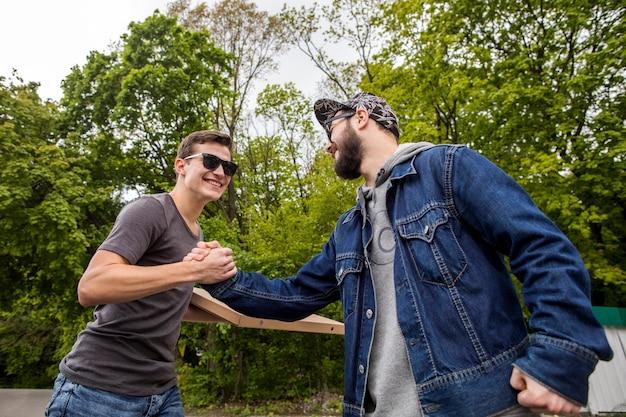 Jonge mannen verwelkomen elkaar in de natuur
