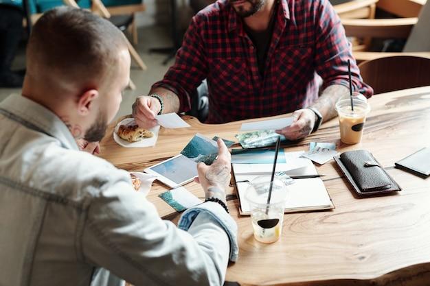 Jonge mannen zitten aan een houten tafel in café en reis bespreken tijdens het kijken naar prachtige foto's