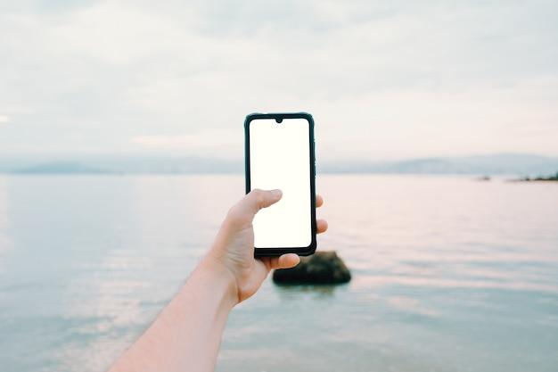 Jonge mannenhand grijpen een telefoon met kopie ruimte verticaal met de oceaan als achtergrond
