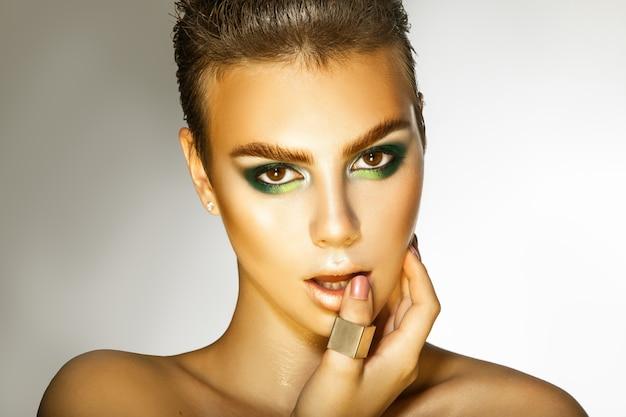 Jonge mannequin met groene kleuren make-up kijken naar camera studio opname grijze achtergrond