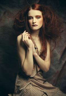 Jonge mannequinvrouw met creatieve make-up zittend op een kruk in dramadecoratie