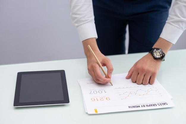 Jonge marketingmanager die nota's over rapport in bureau schrijft