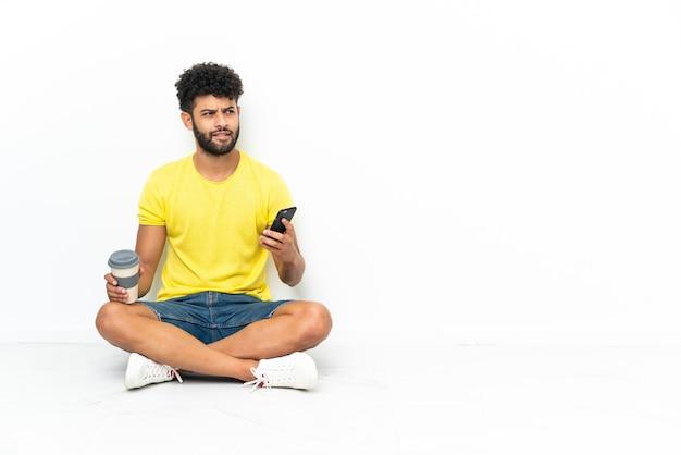 Jonge marokkaanse knappe man zittend op de vloer over geïsoleerde achtergrond koffie te houden om mee te nemen en een mobiel terwijl hij iets denkt
