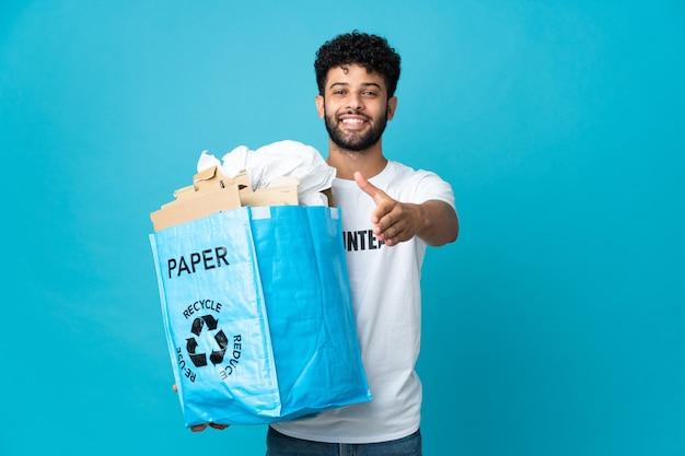 Jonge marokkaanse man die een recyclezak vol papier vasthoudt om over een geïsoleerde muur te recyclen en handen schudt voor het sluiten van een goede deal
