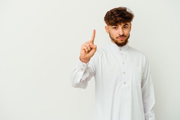 Jonge marokkaanse man die een typische arabische kleding draagt die op witte achtergrond wordt geïsoleerd die nummer één met vinger toont.