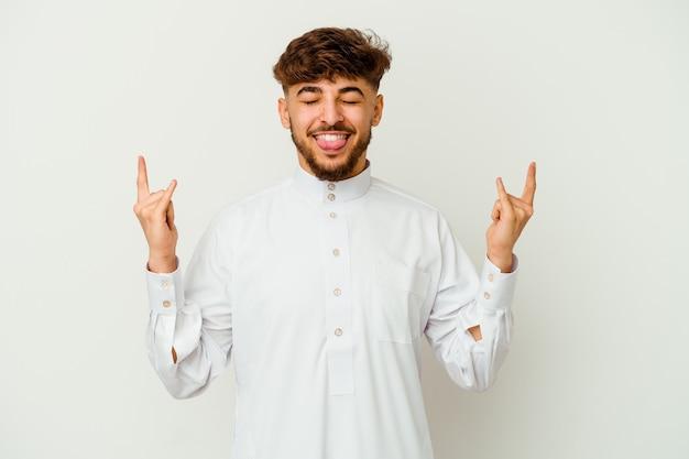 Jonge marokkaanse man die een typische arabische kleding draagt die rotsgebaar met vingers toont