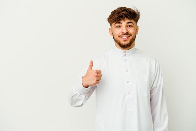 Jonge marokkaanse man die een typische arabische kleding draagt en duim opheft