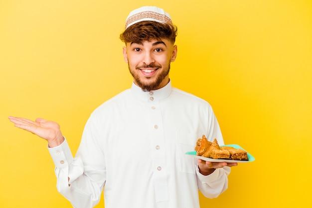 Jonge marokkaanse man die het typische arabische kostuum draagt dat arabische snoepjes eet die op gele achtergrond worden geïsoleerd die een exemplaarruimte op een palm toont en een andere hand op taille houdt.
