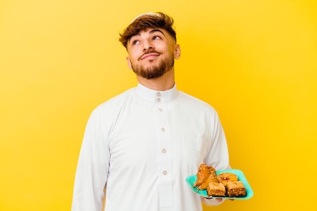 Jonge marokkaanse man die het typische arabische kostuum draagt dat arabische snoepjes eet geïsoleerd op een gele achtergrond, droomt van het bereiken van doelen en doeleinden