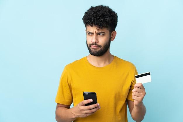 Jonge marokkaanse man geïsoleerd op blauwe muur kopen met de mobiel met een creditcard terwijl hij nadenkt