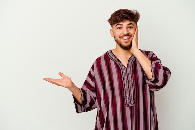 Jonge marokkaanse man geïsoleerd op een witte achtergrond houdt kopie ruimte op een handpalm, hand over de wang houden