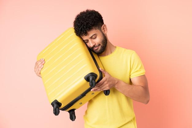 Jonge marokkaanse man geïsoleerd op roze achtergrond in vakantie met reiskoffer en ongelukkig
