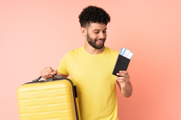 Jonge marokkaanse man geïsoleerd op roze muur in vakantie met koffer en paspoort