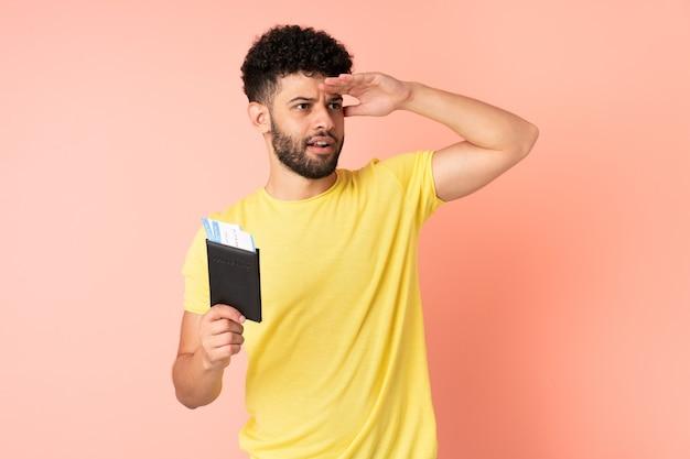 Jonge marokkaanse man geïsoleerd op roze muur in vakantie met paspoort en vliegtickets terwijl hij iets in de verte kijkt