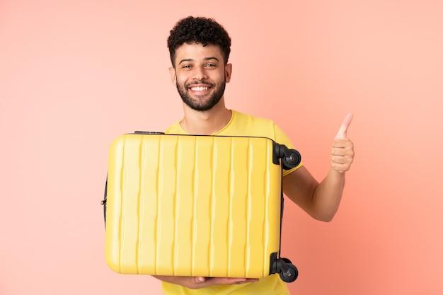 Jonge marokkaanse man geïsoleerd op roze muur in vakantie met reiskoffer en met duim omhoog