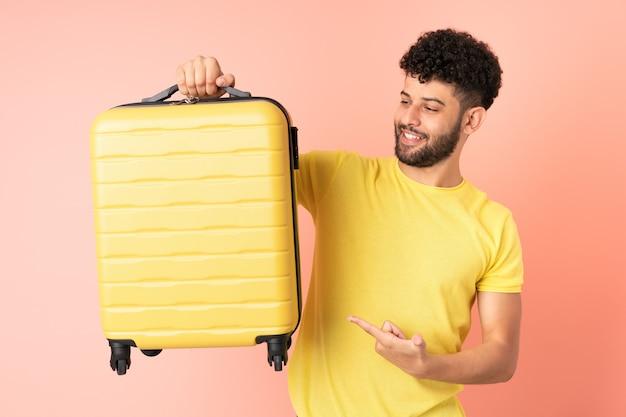 Jonge marokkaanse man geïsoleerd op roze muur in vakantie met reiskoffer