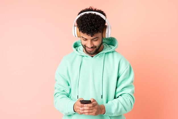 Jonge marokkaanse man geïsoleerd op roze muur muziek luisteren en op zoek naar mobiel