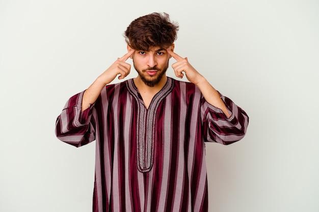 Jonge marokkaanse man geïsoleerd op wit concentreerde zich op een taak, met wijsvingers wijzend hoofd.