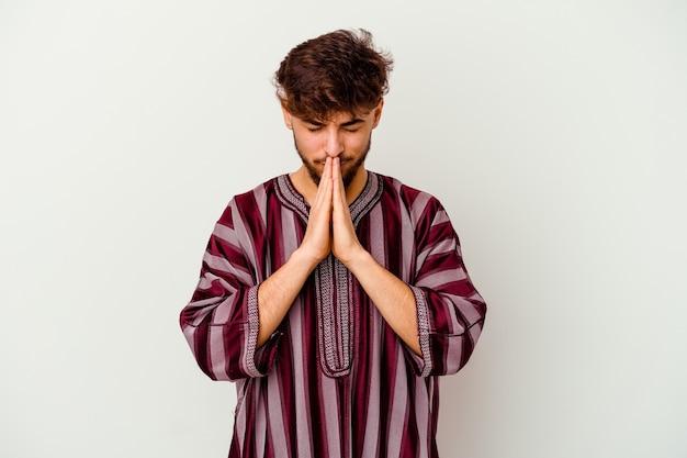 Jonge marokkaanse man geïsoleerd op wit hand in hand bidden in de buurt van de mond, voelt zich zelfverzekerd.