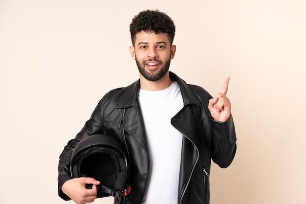 Jonge marokkaanse man met een motorhelm geïsoleerd op beige muur denken een idee met de vinger omhoog