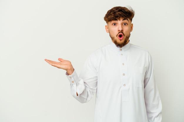Jonge marokkaanse man met een typische arabische kleding geïsoleerd op een witte achtergrond onder de indruk kopie ruimte op palm te houden.