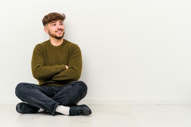 Jonge marokkaanse man zittend op de vloer geïsoleerd op wit glimlachend zelfverzekerd met gekruiste armen.