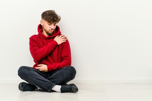 Jonge marokkaanse man zittend op de vloer geïsoleerd op wit met pijn in de schouder.