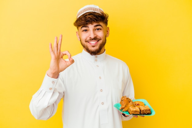 Jonge marokkaanse mens die het typische arabische kostuum draagt dat arabische snoepjes eet die op gele achtergrond worden geïsoleerd vrolijk en zelfverzekerd ok gebaar tonen.