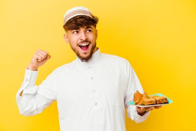 Jonge marokkaanse mens die het typische arabische kostuum draagt dat arabische snoepjes eet die op gele achtergrond wordt geïsoleerd die vuist opheft na een overwinning, winnaarconcept.