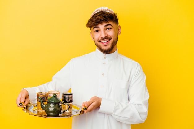 Jonge marokkaanse mens die het typische arabische kostuum draagt dat thee drinkt die op geel wordt geïsoleerd