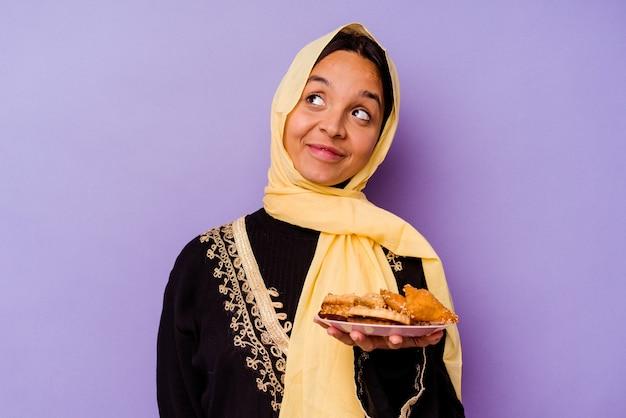 Jonge marokkaanse vrouw die arabische snoepjes houdt die op purpere achtergrond worden geïsoleerd die dromen van het bereiken van doelstellingen en doeleinden