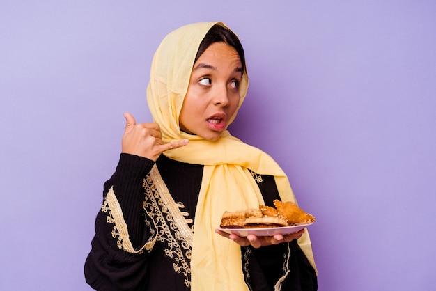 Jonge marokkaanse vrouw die arabische snoepjes houdt die op purpere achtergrond worden geïsoleerd die een mobiel telefoongesprekgebaar met vingers tonen.