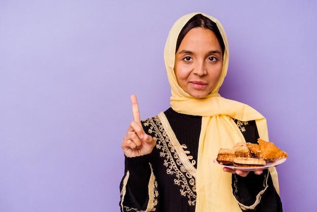 Jonge marokkaanse vrouw die arabische snoepjes houdt die op purpere muur worden geïsoleerd die nummer één met vinger toont.