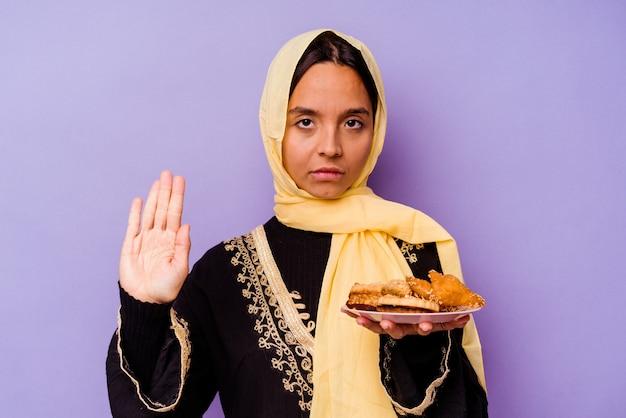 Jonge marokkaanse vrouw die arabische snoepjes houdt die op purpere muur worden geïsoleerd die zich met uitgestrekte hand bevinden die eindeteken tonen, die u verhinderen.