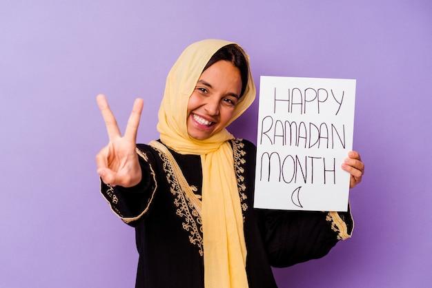 Jonge marokkaanse vrouw die een gelukkig ramadan-aanplakbiljet houdt dat op purpere achtergrond wordt geïsoleerd