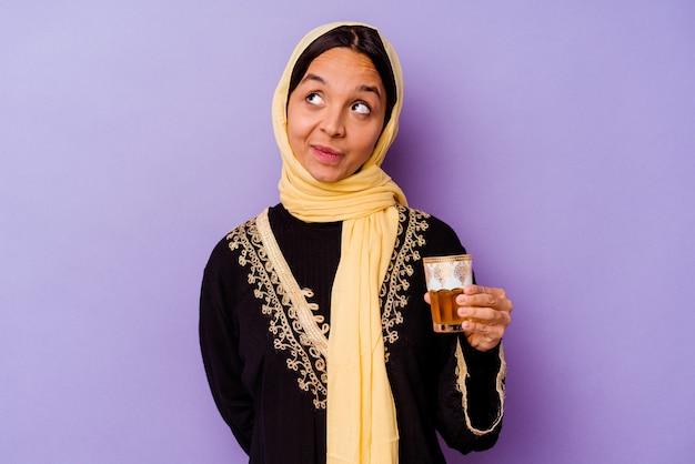 Jonge marokkaanse vrouw die een glas thee houdt dat op purpere achtergrond wordt geïsoleerd die droomt van het bereiken van doelstellingen en doeleinden